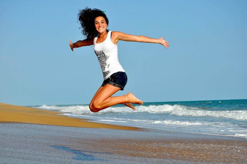 wesola-kobieta-skacze-nad-morzem