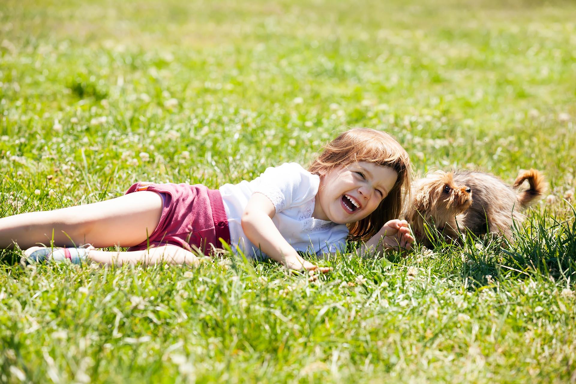 Dziewcznyka-lezaca-na-trawie-z-malym-psem