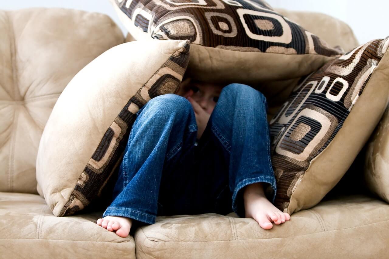 Obrazony-chlopiec-przykryty-poduszkami