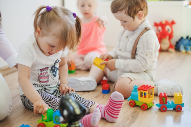 Trójka dzieci bawiąca się na podłodze